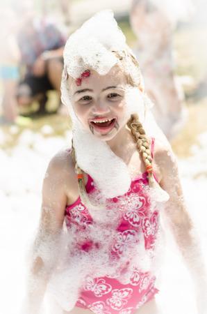foam party: happy blond girl enjoying foam party