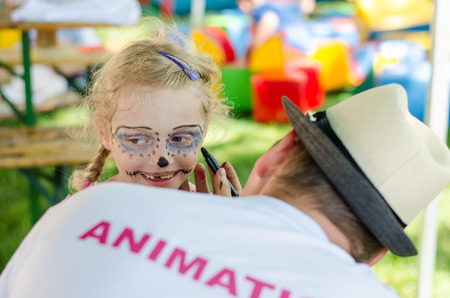 blond girl: blond girl with facepainting and back view of animation team member Stock Photo