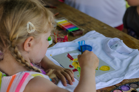 beautiful blond girl painting with brush into t-shirt with colorful colors back view Banque d'images