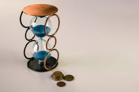 eur: sandglass and eur banknote and coins