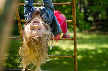 cabello rubio: hermosa chica rubia con el pelo largo que juega en el parque Foto de archivo