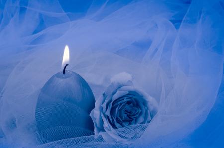 blue burning candle and rose over blue fabric background Standard-Bild