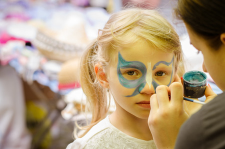 girl with long blond hair with facepainting