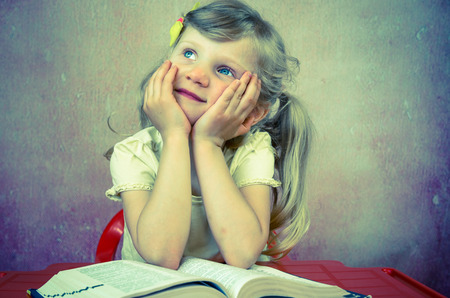 beautiful blond girl over open book photo