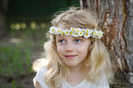 adorable smiling little blond girl with daisy flower headband