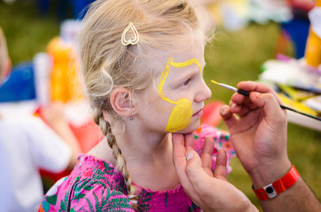 cute blonde: beautiful blond girl waiting to be face-painted Stock Photo