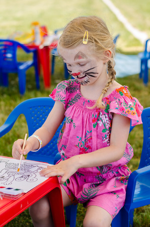 art activity: girl with face-painting of cat drowing with paintbruch Stock Photo