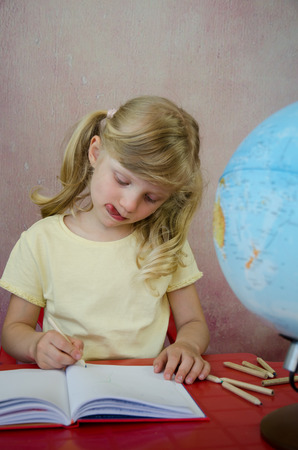 concentrated: beautiful blond child concentrated doing homework