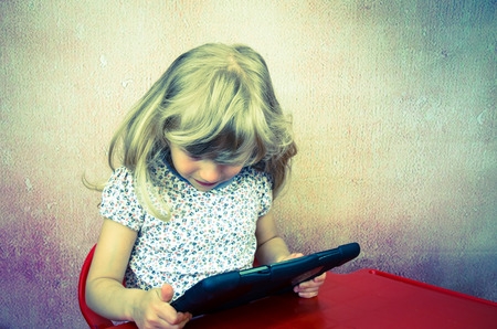blond girl: concentrated little blond girl working with tablet