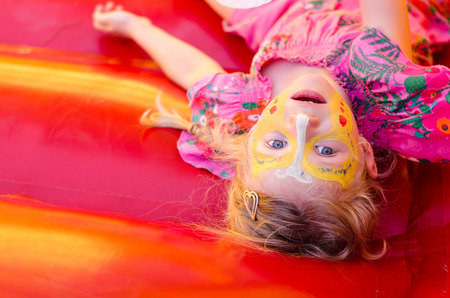 little girl with bright colorful facepainting
