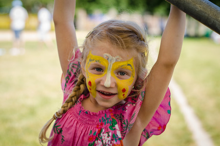 children painting: beautiful blond girl with yellow butterfly face-painting