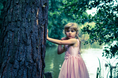 leaned: little blond girl with long hair leaned to the tree trunk