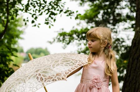blond girl: little blond girl  holding white sunshade