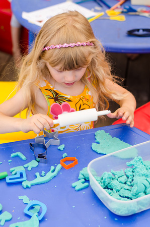 blond girl: beautiful blond girl playing with plasticine Stock Photo