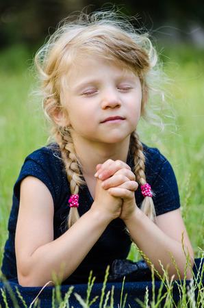 trenzas en el cabello: retrato de la chica rubia con el pelo trenzado rezando