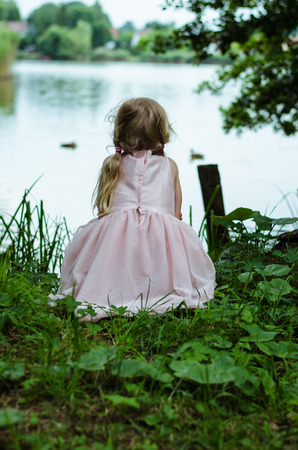 little blond girl crouched by pond rear view