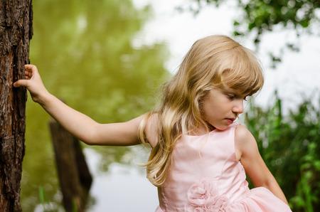 blond girl: little blond girl by tree trunk Stock Photo