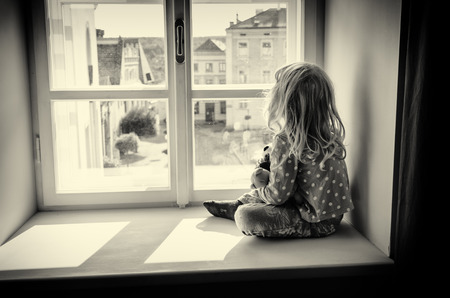 think through: little blond girl sitting and looking over window