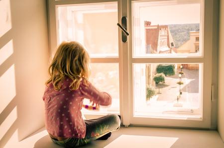 ni�os abandonados: ni�a rubia sentada y mirando por encima de la ventana