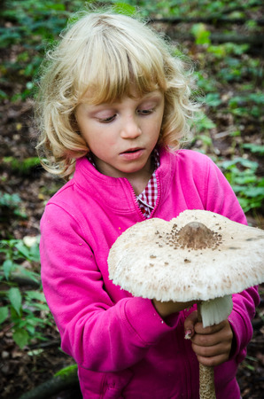 giant mushroom: girl with giant parasol mushroom at autumn time Stock Photo