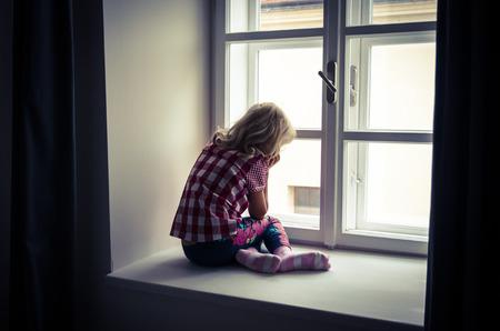petite fille triste: petite fille blonde assise et regarder par-dessus la fen�tre Banque d'images