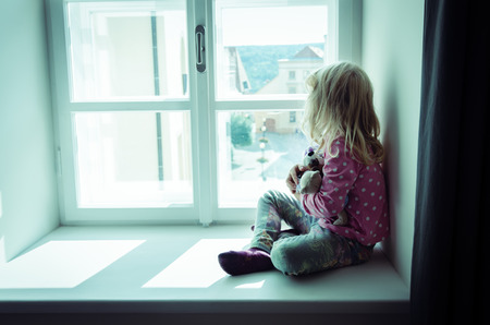 little blond girl sitting and looking over window