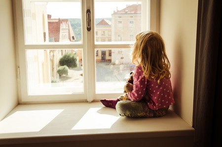 ni�os abandonados: little blond girl sitting and looking over window