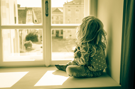 think through: little blond girl sitting and looking over window sepia tonned