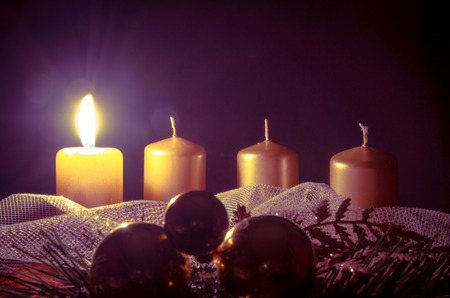 advent wreath with one burning candle against purple background