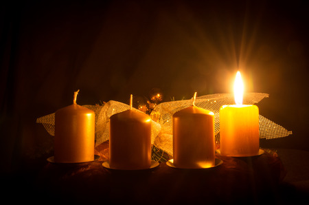 one burning candle in advent wreath