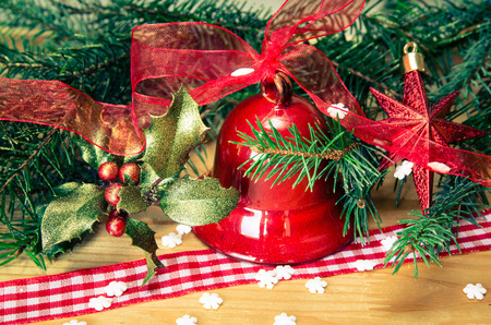traditional plants: Christmas decoration with red jingle bell, holly and green needle branch