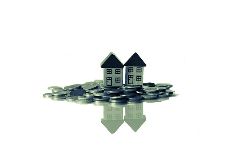 debet: group of coins and a small houses standing on it Stock Photo
