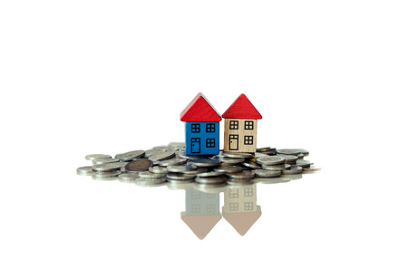 money exchange: group of coins and a small houses standing on it Stock Photo