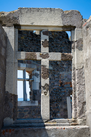 stoned: ancient window with cross in stoned wall Stock Photo