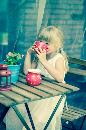 children party: adorable blond girl drinking tea from red dotted teacup