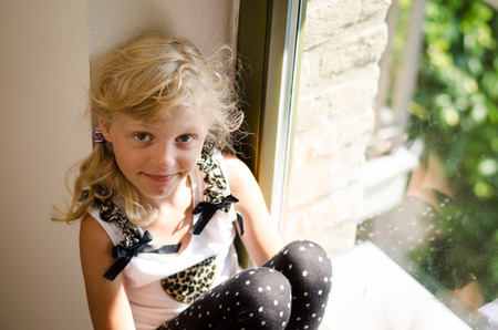 elementary age girls: adorable girl with long blond hair sitting in the window table