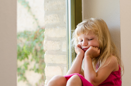 dissapointed: adorable bored girl with long blond hair sitting by the window