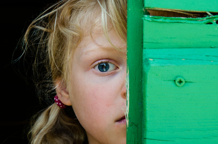 eyes hidden: portrait of girl with big blue eye with hidden half of face