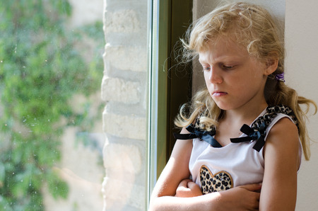 dissapointed: angry girl with long blond hair sitting at the window