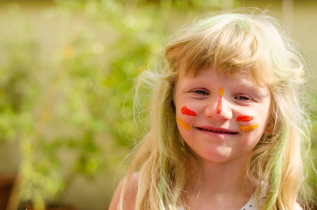 painted face: blond girl with colorful painted face Stock Photo