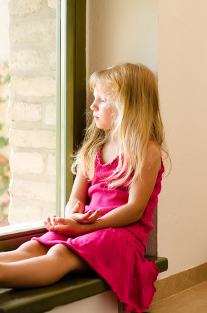 elementary age girl: adorable girl with long blond hair sitting by the window