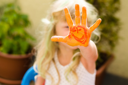 painted hands: blond girl with colorful painted hands Stock Photo