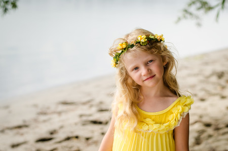 innocent: beautiful blond girl in yellow dress with flower headband by the river strand