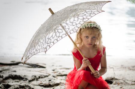 blond meisje met hoofdband in rode jurk van bloemen houdt zonnescherm