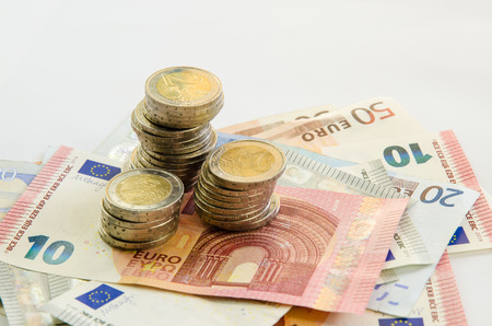 denomination: euro banknotes with different denomination and pile of coins Stock Photo