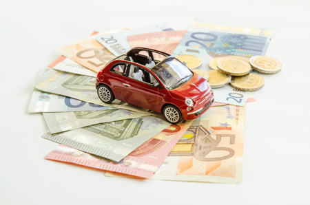 toy car: red toy car on banknotes and coins