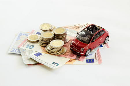 toy car: red toy car and pile of coins Stock Photo