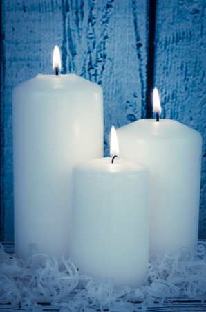 the candle: white burning candles decoration against blue wooden background