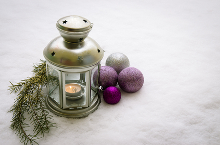 silver lantern with candlelight and silver and purple baubles against snowy background Standard-Bild