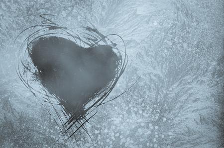 corazones azules: la forma del corazón rayado en el patrón de helada en la ventana